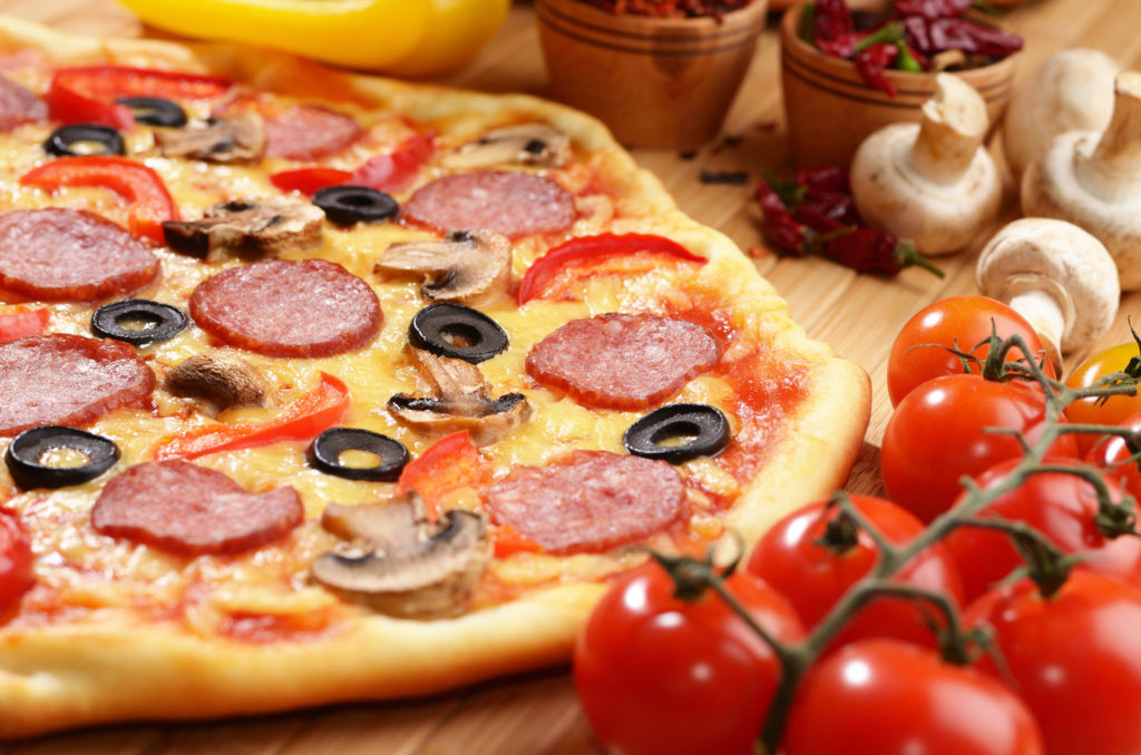 Pepperoni pizza with cherry and mushrooms on the bamboo kitchen table