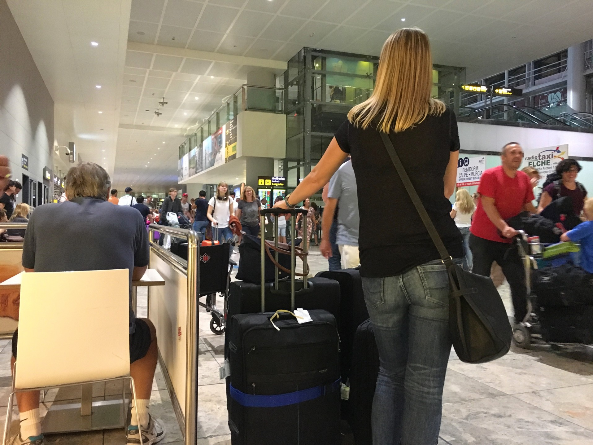 woman-waiting-with-wheelie-suitcases-in-the-arrivals-area-of-el-altet-airport-alicante-spain_t20_nojwlA